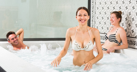 Relaxing smiling friends enjoying in jacuzzi in spa salon