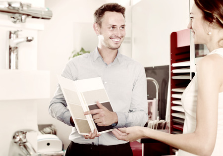 Joyful assistant working with customer in kitchen furniture  store