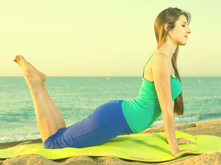 Woman in blue T-shirt is practicing stretching on the beach. Stock fotó