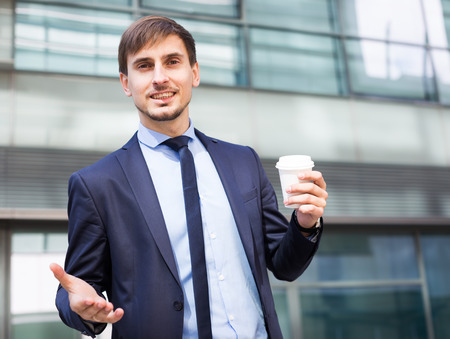 Portrait of cheerful male standing outdoor drinking coffee
