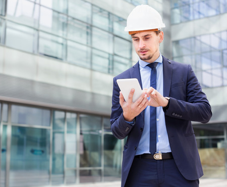 Man architect in helmet working at the tablet outdoors