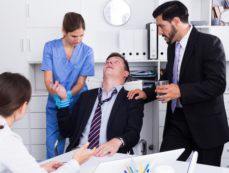 Businessman in fainting receiving first aid at workplace in office