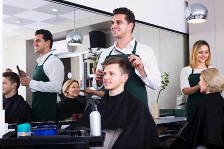 woman mirror: Positive adult male hairdresser cutting hair of teenage guy in barbershop