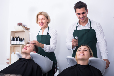 19's: Two positive smiling hairdressers washing hair of clients at salon  . Selective focus on girl Stock Photo