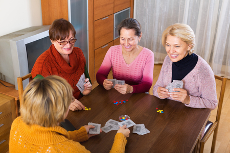 Happy mature woman having fun with pack of cards indoor Stock Photo