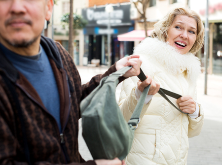 Adult man pulling female bag, outdoors robbery at day time Stock Photo