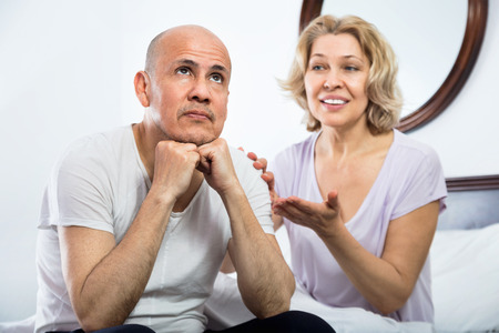Calm tranquil mature  girlfriend consoling grieving man sitting apart Stock Photo