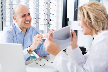 woman mirror: Professional female optician consulting mature smiling male customer about frames