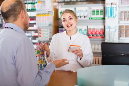 Farmacista farmacista femminile che consiglia sulle droghe che utilizzano nell & # 39 ; armadio moderna