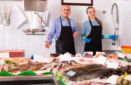 Fish and seafood store with two cheerful smiling sellers in aprons at the counter. Focus on man