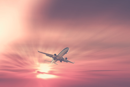 Big civil passenger plane flying up in sky at sunrise time Stock Photo