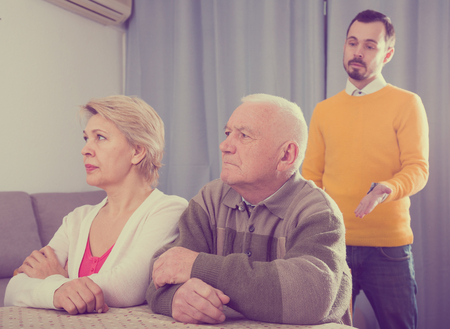 Aged parents arguing with their adult son at home Stock Photo