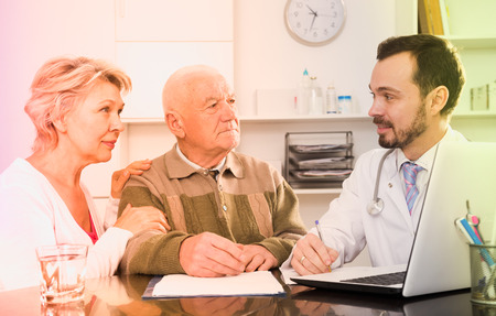 Old father with mature daughter visit doctor for consultation