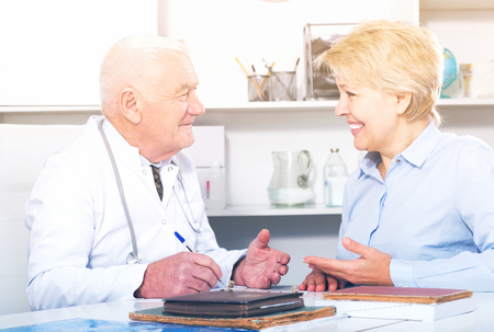 Aged female client having consultation with man doctor in hospital