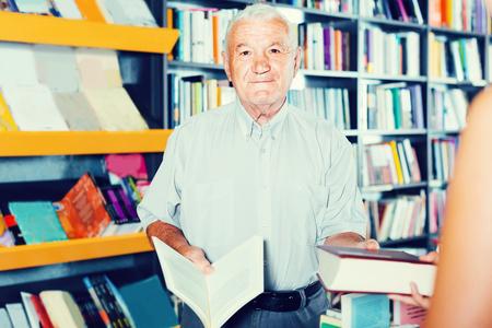 De rijpe Amerikaanse mens koopt boek in boekhandel