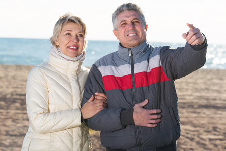Smiling married couple walk and husband points to wife to something interesting Stock Photo