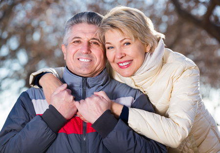 Smiling husband and wife warmly embracing and resting together outdoors
