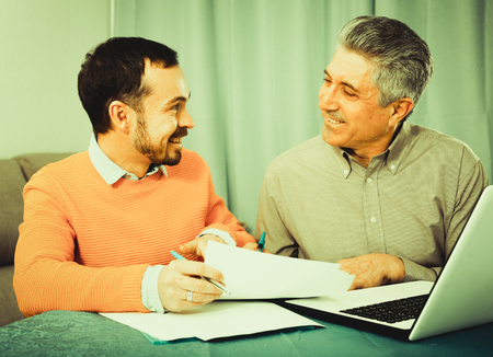 questions: Young man and sales manager discuss terms of contract of purchase at home Stock Photo