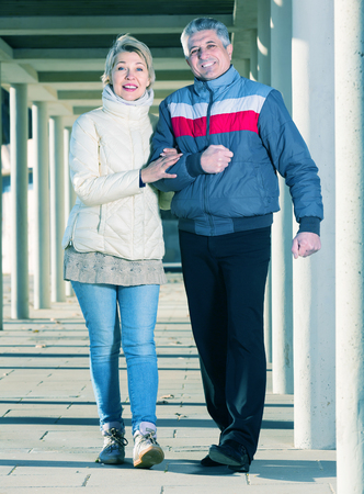 Husband and wife are walking together clear sunny day between columns Stock Photo