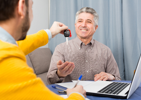 Adult man and manager signed contract car hire at home and hand over keys