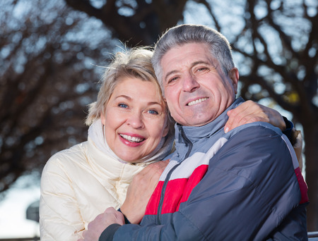 Mature couple hugging each other in park and are happy together. Focus on both persons Stok Fotoğraf