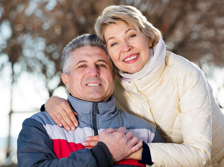 Portrait senior married couple embracing on sunny day in park