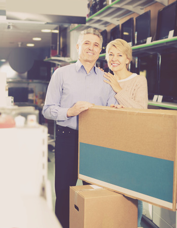 splurge: cheerful mature married couple in shop packed household appliances into boxes for transportation to themselves home