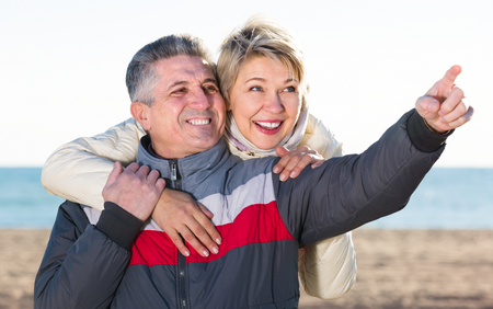 middle-aged husband and wife have together rest and show each other hands interesting things outdoors Stock Photo
