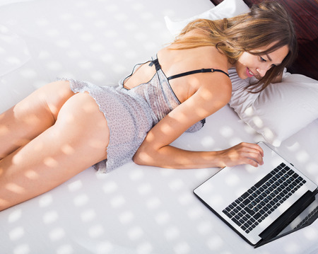 young sexy woman in underwear lying in bed with laptop Stock Photo