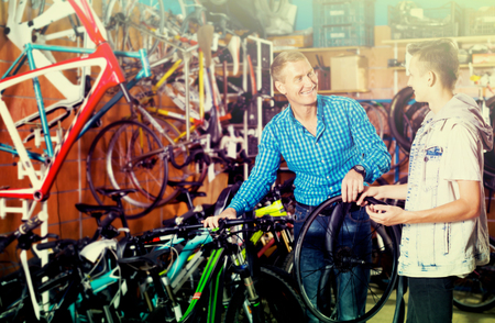 Father 40-45 years old and his son teenager choosing new wheel lid for bicycle in sport hypermarket