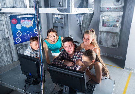 Parents with children are solving puzzles on computer in escape room stylized like laboratory. Stock Photo
