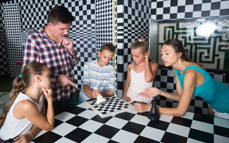 Young family is visiting of escape room stylized under chessboard. Stock Photo