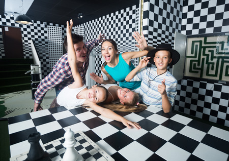 Portrait of family who is satisfied of visit of entertainment styling chessroom. Stock Photo