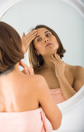 Young woman looking in mirror in bedroom in morning