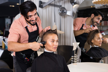 masculin: Smiling adult man professional shaving womans hair in hairdressing salon Stock Photo