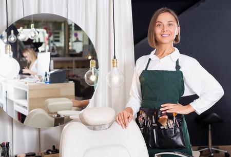 mirror image: Smiling adult female professional visagiste standing indoors