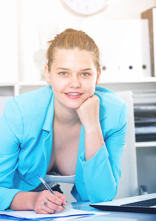 Office worker woman is signing agreement papers of financial nature at office.