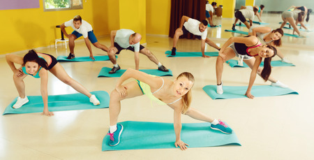 Group of young positive people exercising in dance hall