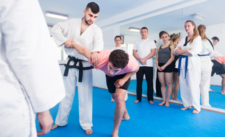 happy american  man training new taekwondo holds with adults during class