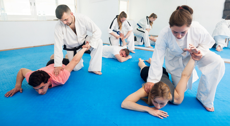 Positive adults training in pairs to practice new holds at taekwondo class Stock Photo