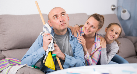 family sofa: Tired father sitting near the table with mop after cleaning home