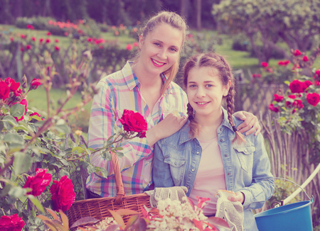 smiling american woman and teen holding a basket and standing in the park of roses. Stock Photo