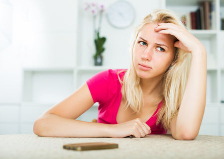 Young blond girl looking annoyed and waiting for call on mobile phone indoors Stock Photo