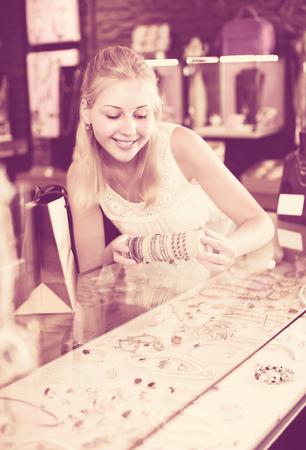 portrait of cheerful smiling blonde girl choosing bracelet in shop with bijouterie