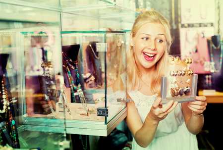 woman mirror: Portrait of young friendly cheerful woman choosing earrings in shop with bijouterie Stock Photo