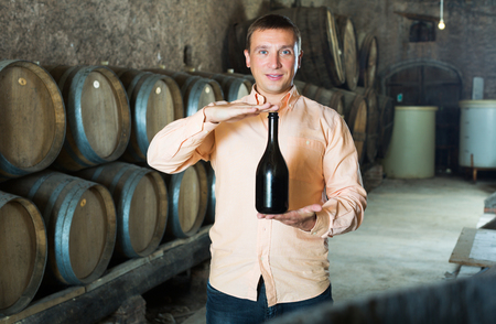 Satisfied customer holding bottle of red wine from wooden barrels
