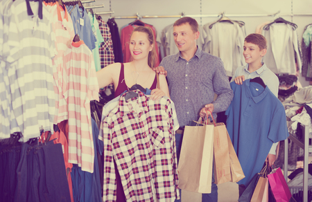 smiling young family stands near clothes and choosing man shirt in store