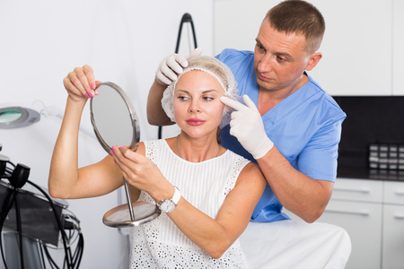 Man ドクターは、女性患者をキャビネット内の処置に準備しています。 写真素材