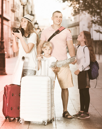 Positive tourist family with kids using map and  making amateur photo of sights in Europe city