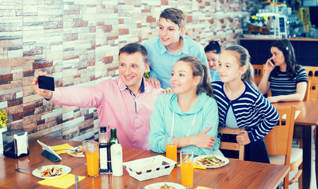 Adult family of four with teenage children taking selfie in cafe